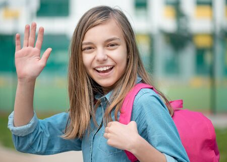 Schoolchild go to school with backpack. Cute child - teen girl with bag stretching her right hand up for greeting. against the background of school. Back to school concept.