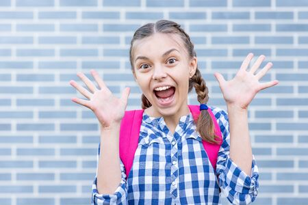 Beautiful student teenager schoolchild with backpack having fun. Cheering cute child with bag. Teen girl with braided hair against a brick wall outdoors. Childhood and Back to school concept.