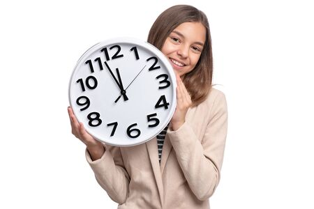 Portrait of beautiful Teen Girl holding big Alarm Clock, isolated on white background. Child Back to School, Educational and Time Concept. Time is running out.