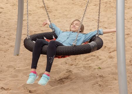 Happy teen girl on swing in playground outdoors. Beautiful student teenager swinging on swing in summer park. Child having fun after school lessons. Childhood and Back to school concept.