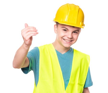 Funny Handsome Teen Boy wearing Safety Jacket and yellow Hard Hat. Portrait of Happy Child Makes Hand Gesture and Looking at Camera, isolated on white background.