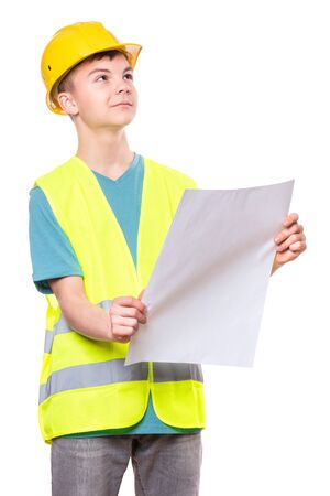 Funny Handsome Teen Boy wearing Safety Jacket and yellow Hard Hat. Happy Child Holding and Reading a Plan, isolated on white background.