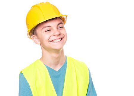 Funny Handsome Teen Boy wearing Safety Jacket and yellow Hard Hat. Portrait of Happy Child Smiling and Looking away, isolated on white background.