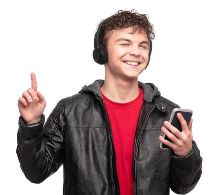 Portrait of Handsome brutal Teen Boy in black Leather Jacket with headphones. Fashion Child Model isolated on White background. Funny Teenager using mobile phone and listening to music.