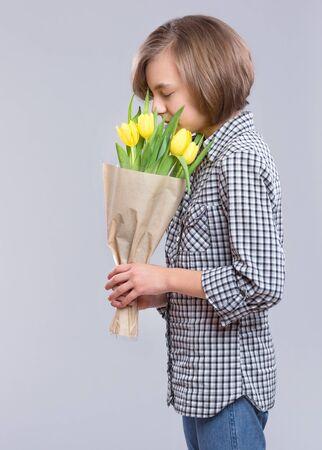 有束的美丽的女孩在灰色背景的花。有黄色郁金香花束的微笑的孩子作为礼物。母亲,生日或情人节快乐。