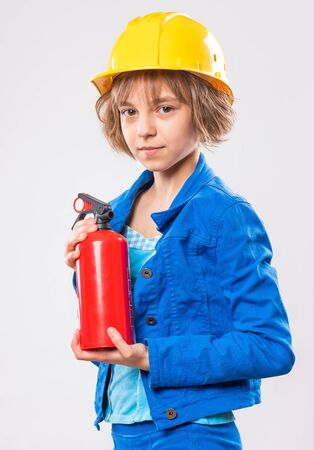 Emotional Portrait of attractive caucasian Girl wearing safety yellow Hard Hat. Beautiful Child holding a Fire Extinguisher on gray background.