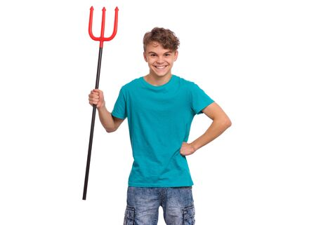 Happy halloween concept. Smiling teen boy holding red trident, isolated on white background. Joyful young teenager looking at camera. Funny child with plastic toy celebrates autumn holiday. Foto de archivo