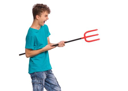 Happy halloween concept. Screaming teen boy holding red trident, isolated on white background. Joyful young teenager looking away. Funny child with plastic toy celebrates autumn holiday. Reklamní fotografie