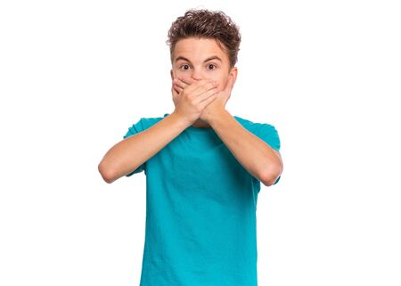 Portrait of amazed teen boy covers his mouth with hands. Child with very large eyes in surprise looking at camera. Caucasian young teenager, isolated on white background. Speak no evil concept.