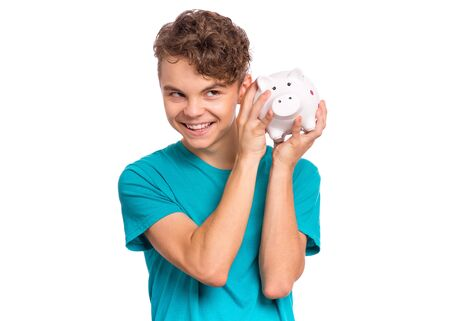 Portrait of teen boy holding and shaking Piggy Bank. Caucasian teenager isolated on white background. Saving Money concept. Happy child smiling and trying to figure out how much money he has saved. 版權商用圖片