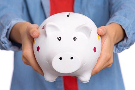 Nahaufnahme der Kinderhände, die Sparschwein halten. Geld sparen Konzept. Standard-Bild