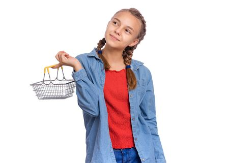 Portrait of teen girl holding small shopping basket, isolated on white background. Happy child with mini empty shopping basket. Sale, consumerism and people concept. Schoolgirl is ready to go shopping