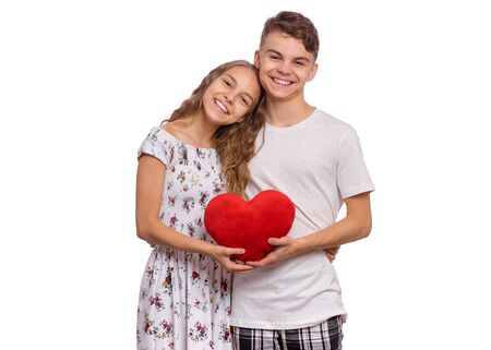 Portrait of sweet young couple in love. Happy teen boy and girl standing together, holds plush heart in hands. Hugging smiling teenagers with symbol of love, family, hope. Friendship and love concept