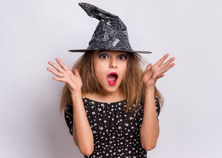 Gelukkig halloween-concept. Verrast tiener meisje in zwarte heks hoed kijken camera in verbazing op grijze achtergrond. Schattig kind in heks halloween kostuum schreeuwen, ogen en mond openen met schok.