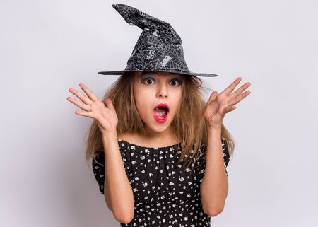Happy halloween concept. Surprised Teen girl in witch black hat looking at camera in amazement on grey background. Cute child in witch halloween costume shouting, opening eyes and mouth with shock.