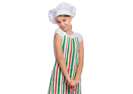 Portrait of beautiful shy teen girl in chef hat, isolated on white background. Portrait of cute child cook in apron, posing in studio, looking at camera.