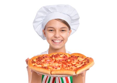 Happy beautiful teen girl in chef hat holding cooked pizza. Girl cook in apron holds plate with fresh pizza, isolated on white background. Portrait of cute child showing delicious Italian pizza. Stock Photo