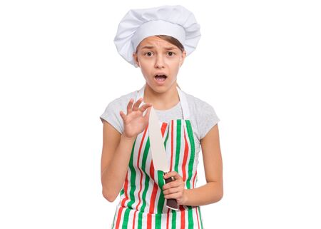 Portrait of beautiful young teen girl holding big sharp knife, isolated on white background. Cute child cook in apron hurt her finger. Tools and equipment for cooking.