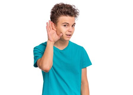 Portrait of teen boy holds his hand near his ear and listening something, isolated on white background. Cute caucasian young teenager overhears, listening an hearing to rumor or gossip. Stok Fotoğraf