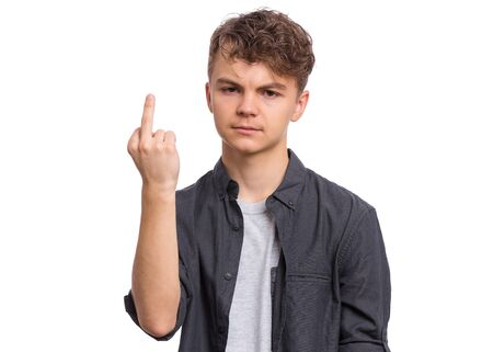 Portrait of angry teen boy showing middle finger, isolated on white background. Handsome caucasian young teenager showing bad gesture. Upset cute child doing obscene sign.