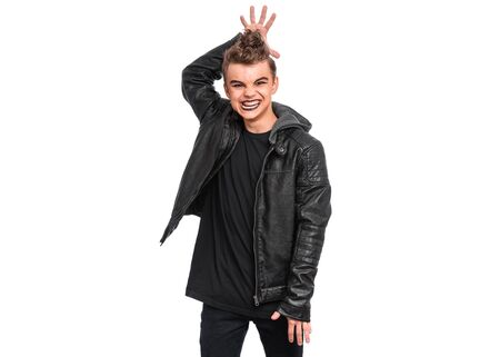 Rebellious teen boy dressed in black making horns with fingers on head, isolated on white background. Teenager in style of punk goth wearing leather jacket. Problems of transition age.