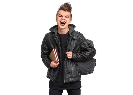 Portrait of teen boy student with spooking make-up, isolated on white background. Teenager with backpack in style of punk goth dressed in black screaming and shouting. Problems of transitional age. Banco de Imagens - 130095083