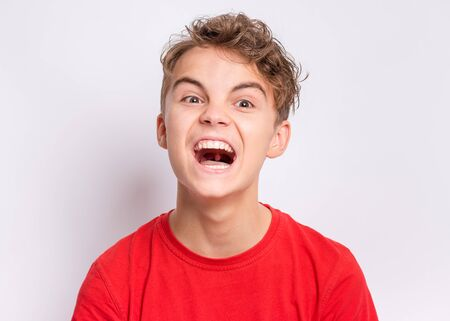 Emotional portrait of upset and angry screaming teen boy on grey background. Child looking camera with angry facial expression. Handsome caucasian young teenager with problems.