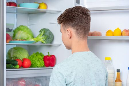 Back view - young teen boy standing near open fridge in kitchen at home. Portrait of pretty child choosing food in refrigerator full of healthy products - rear view. Stock Photo