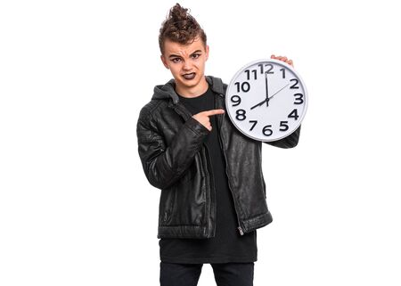 Teen boy student with spooking make-up holds big Clock, isolated on white background. Teenager in style of punk goth dressed in black back to school. Child making grimace. Education and time concept.
