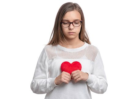 UnHappy Valentines Day. Cute upset Teen Girl with Eyeglasses in Love with Red plush Heart in her hands. Sad Child, isolated on white background.
