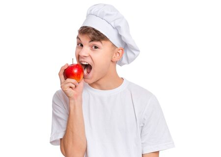 Happy teen boy in chef hat holding and eats fresh red apple, isolated on white background. Portrait of smiling child cook bites delicious fruit. Organic natural healthy food produce.