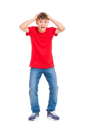 Cute child covered his head with his hands. Full length portrait of caucasian teen boy. Funny shocked teenager isolated on white background. Handsome child looking at camera.