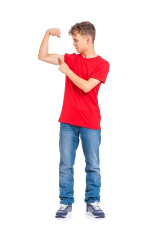 Full length portrait of young caucasian teen boy isolated on white background. Funny teenager wearing red t-shirt showing off his biceps. Handsome child showing his hand biceps muscles strength.