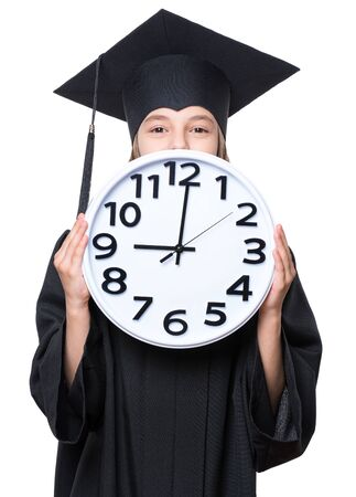 Portrait of a graduate girl student in a black graduation gown with hat, holding big clock - isolated on white background. Child back to school, educational and time concept.