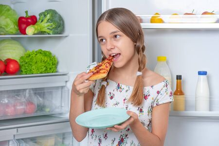 Hungry beautiful young teen girl eats slice of pizza while standing near open fridge in kitchen at home. Portrait of pretty child choosing food in refrigerator full of healthy products.