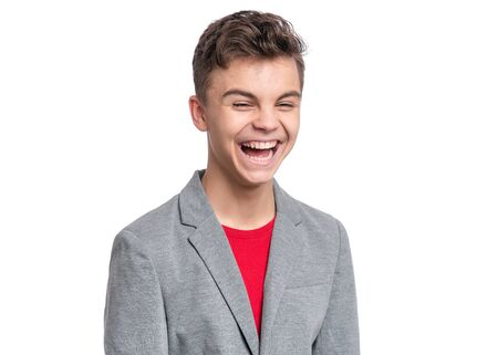 Handsome Teen Boy in gray suit. Portrait of caucasian Smiling Teenager isolated on white background. Happy child having fun.