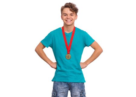 Happy winner. Portrait of Handsome Teen Boy Student holding gold Medal. Smiling child celebrating his success, isolated on white background. Back to School or sport concept. 版權商用圖片