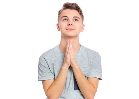 Portrait of teen boy praying, isolated on white background. Cute caucasian teenager with hands folded in prayer hoping for better. Child asking God for good luck, success or forgiveness. Looking up.