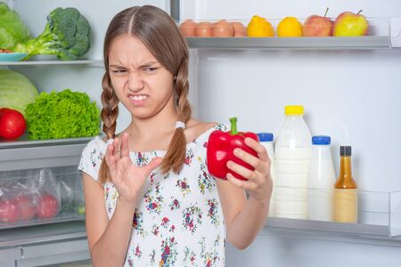 Teen girl holding fresh red pepper while standing near open fridge in kitchen at home. Child do not want to eat vegetables and dislike taste of pepper. Organic natural healthy food produce. Stock Photo