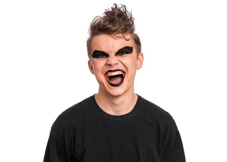 Rebellious teen boy dressed in black, isolated on white background. Angry screaming teenager in style of punk goth wearing black t-shirt, shouting. Problems of transitional age.