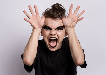 Crazy teen boy with spooking make-up making horns with fingers on head, on grey background. Teenager in style of punk goth dressed in black screaming and shouting. Problems of transitional age.