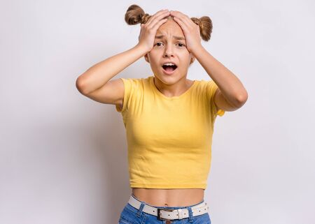 Portrait of surprised teen girl, on gray background. Funny child looking at camera in amazement, touching head with hands. Beautiful caucasian teenager, opening eyes and mouth with shock, screaming. 免版税图像