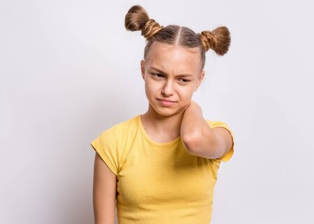 Unhappy teen girl suffering from neck ache, on grey background. Cute young teenager hands touching neck pain. Upset child massaging neck suffering from discomfort ache pain.