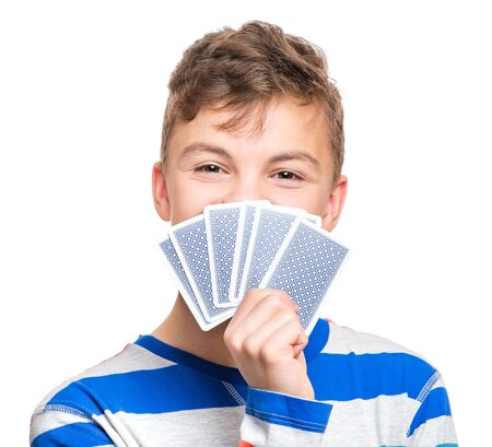 Close up portrait of caucasian teen boy with gamble cards. Handsome guy showing collect cards. Funny cut teenager playing, isolated on white background. Childhood concept - free time, fun and hobby. Standard-Bild - 143295845