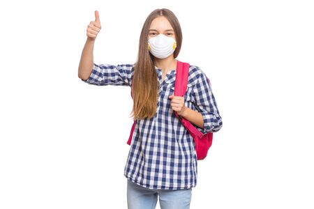 Concept of coronavirus quarantine. Child wearing medical protective face mask to health protection from influenza virus. COVID-19. Student teen Girl with bag making Thumb up Gesture, isolated on white Banque d'images