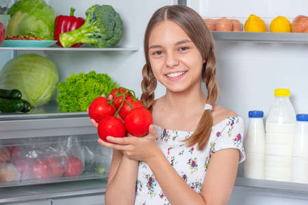 Smiling beautiful young teen girl holding fresh red tomatoes while standing near open fridge in kitchen at home. Portrait of pretty child choosing food in refrigerator full of healthy products