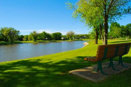 Banca del parque con vistas a un lago Foto de archivo