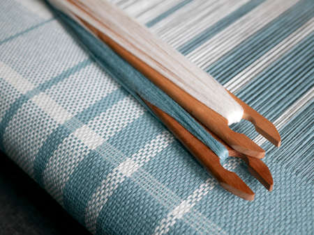 Two shuttles with turquois and white yarn are on the weaving loom. Woven striped fabric Banque d'images
