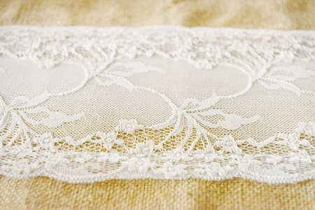 Close up of a lace of a white table runner on a beige linen fabric