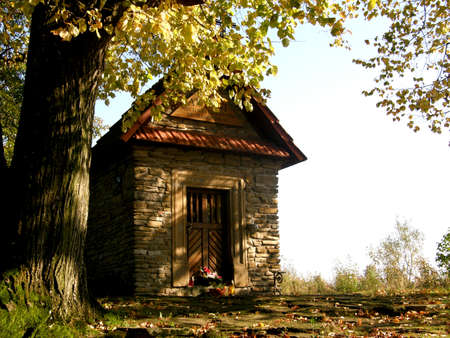 a photo showing a small stone chapel by the road standing under a tree
